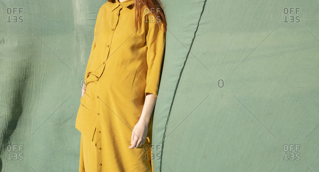 Model wearing yellow outfit in front of a blue cloth backdrop