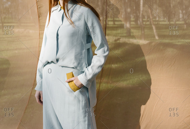 Young woman wearing light blue outfit in front of a tan drop cloth