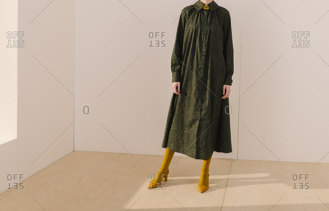 Model wearing a dark green leafy pattern dress with yellow tights and shoes