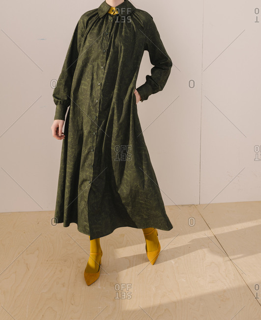 Young woman wearing a dark green leafy pattern dress with yellow tights and shoes