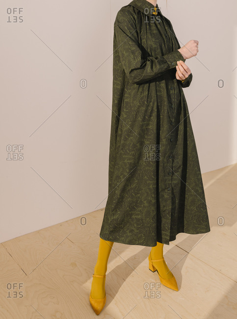 Stylish woman wearing a dark green leafy pattern dress with yellow tights and shoes