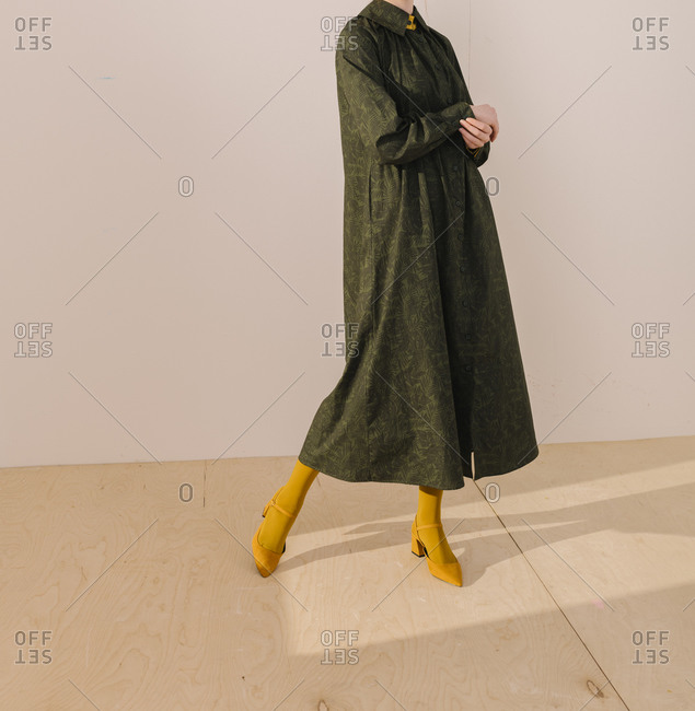 Studio shot of woman wearing a dark green leafy pattern dress with yellow tights and shoes