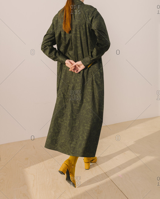 Back view of woman wearing a dark green leafy pattern dress with yellow tights and shoes