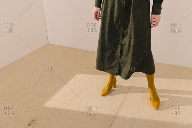 Low-section of woman wearing a dark green leafy pattern dress with yellow tights and shoes