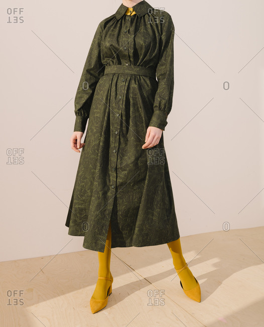 Woman wearing a belted dark green leafy pattern dress with yellow tights and shoes