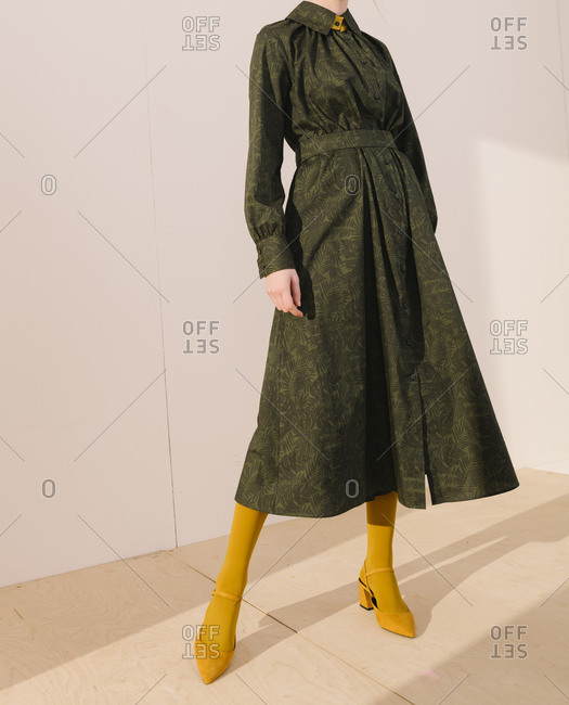 Young woman wearing a belted dark green leafy pattern dress with yellow tights and shoes