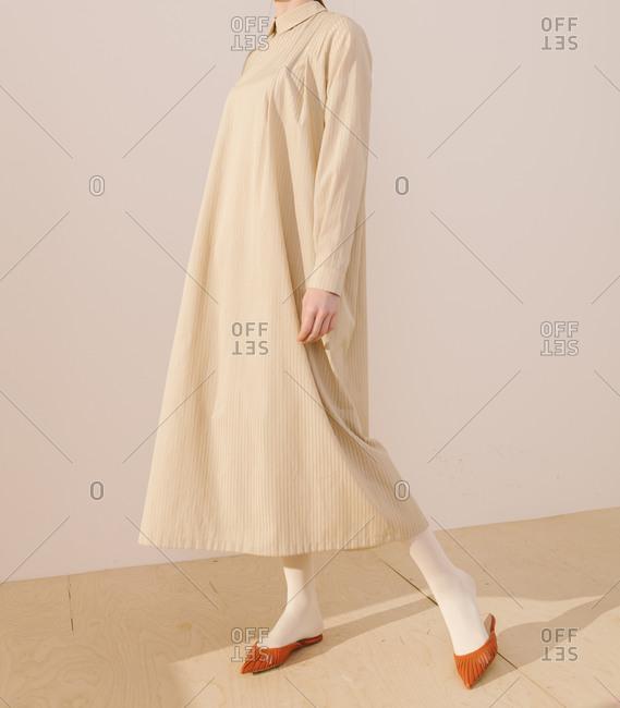 Studio shot of model wearing a long striped yellow dress