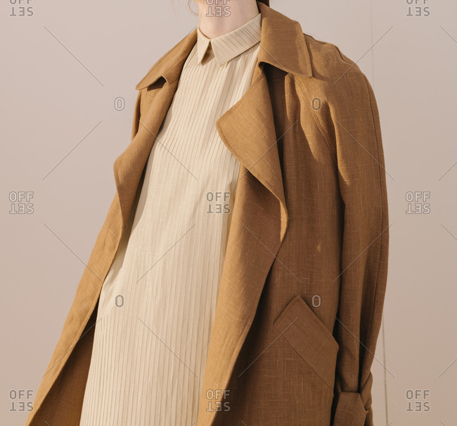Mid-section of model wearing a long striped yellow dress covered by a brown trench coat