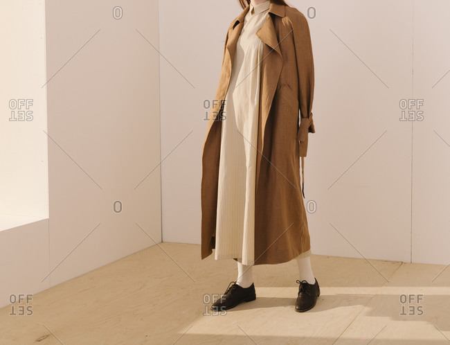 Model wearing a long striped yellow dress covered by a brown trench coat