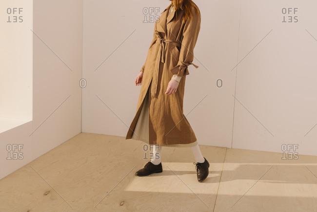 Studio shot of a model wearing a long brown trench coat