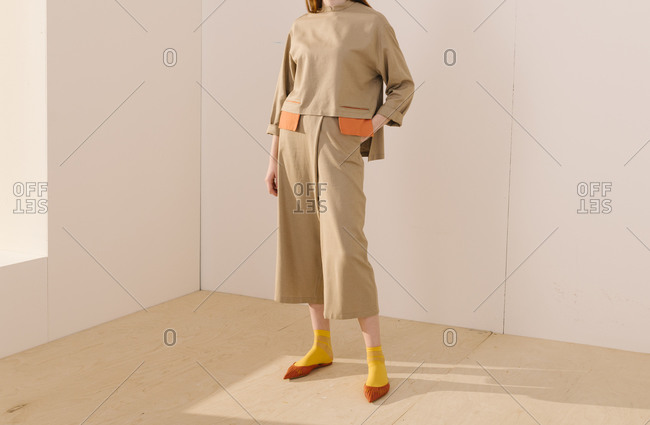 Model wearing casual tan and orange outfit with yellow socks