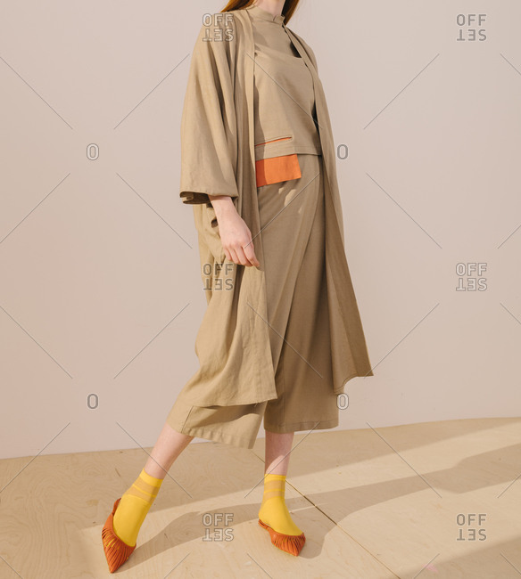 Young model wearing casual tan and orange outfit with yellow socks