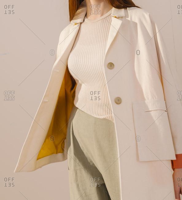 Stylish woman wearing a white jacket with yellow lining