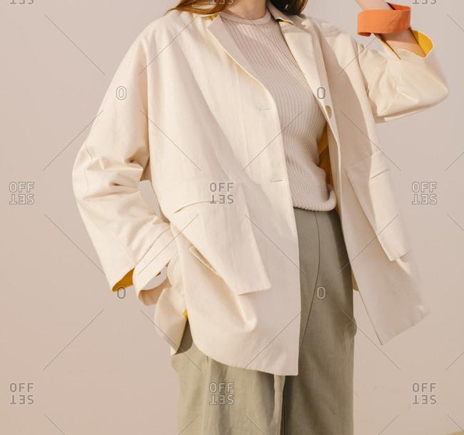 Stylish woman wearing a white jacket and gray pants