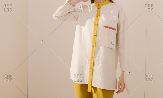 Model wearing a white and yellow collared shirt with matching yellow pants