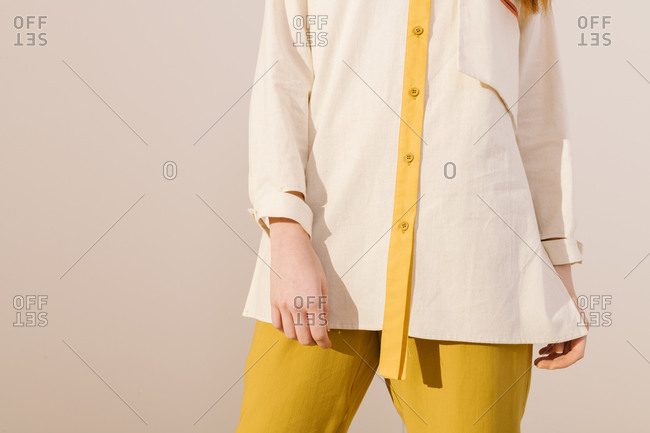 Close up of a model wearing a white and yellow collared shirt with yellow pants
