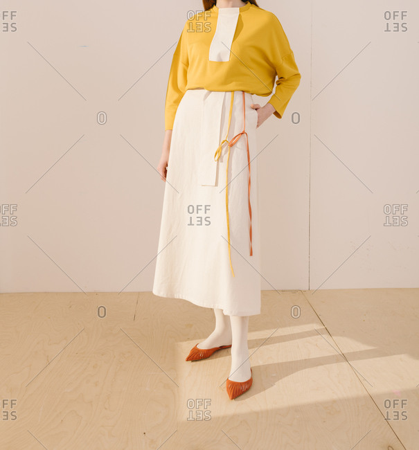 Studio shot of model wearing a white skirt with a yellow top