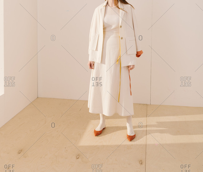 Studio shot of model wearing a white outfit with yellow and orange accents