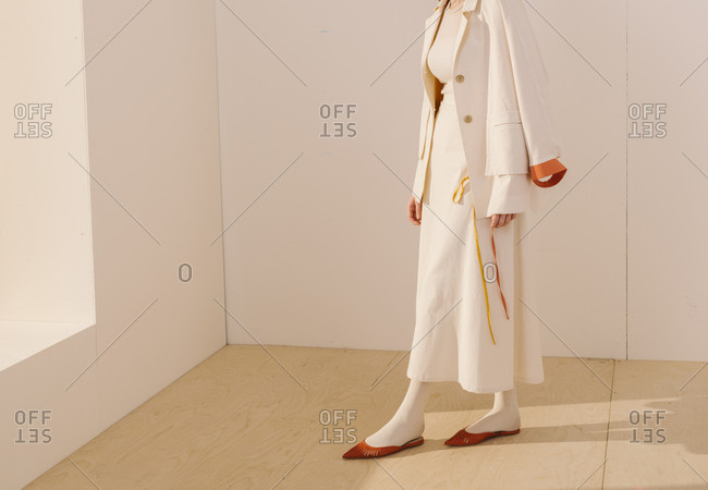 Side view shot of model wearing a white outfit with yellow and orange accents
