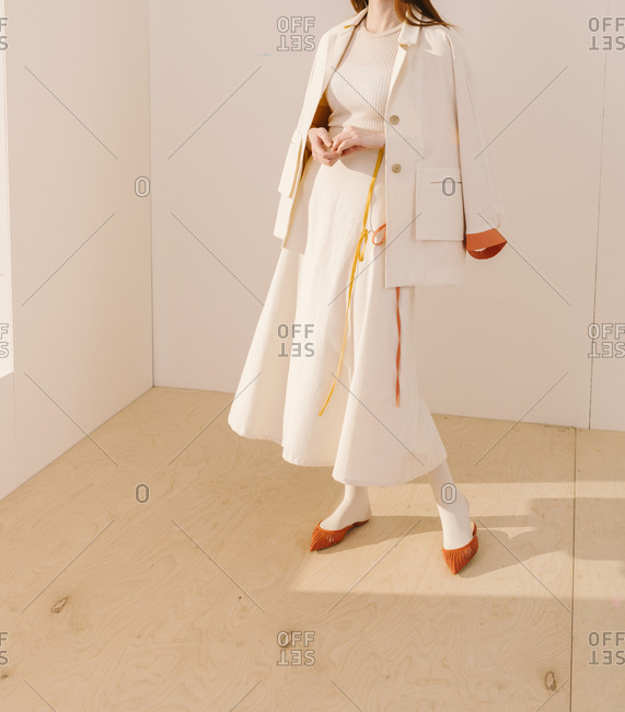 Model wearing a white outfit with yellow and orange accents