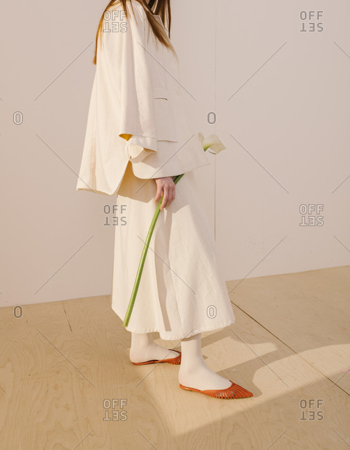 Side view of a model wearing a white outfit with yellow and orange accents holding a calla lily