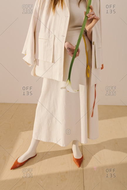 Model wearing a white outfit with yellow and orange accents holding a calla lily