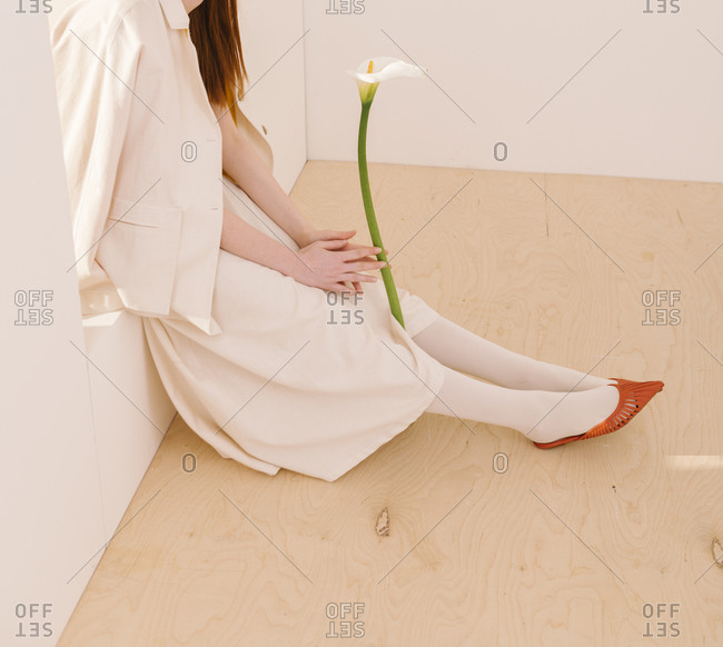 Studio shot of a woman wearing a white outfit sitting and holding a calla lily