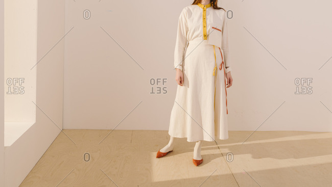 A model wearing a white outfit with yellow and orange accents