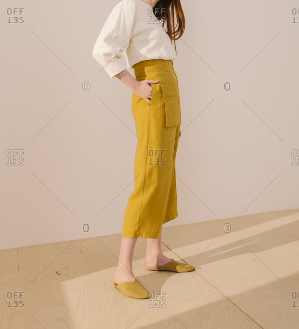 Young woman wearing bright yellow capri pants and matching shoes
