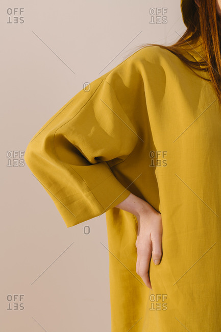 Stylish woman wearing bright yellow long dress and placing her hand on her hip