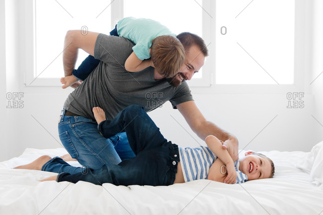 Happy father playing with smiling boys on bed