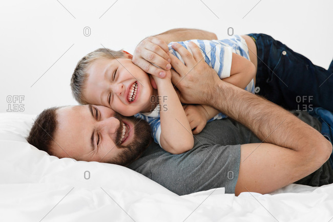 Father and son cuddling and laughing together on bed