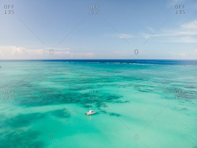 Aerial view of a small boat in the Indian Ocean, just off the coast of Nungwi Beach, Zanzibar