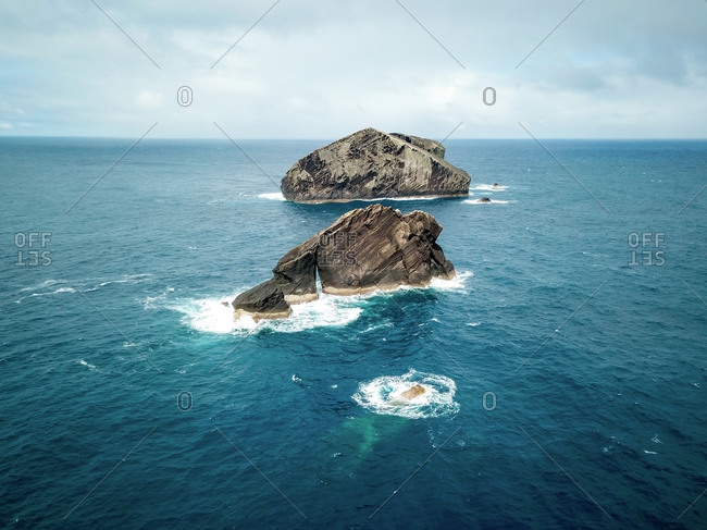 Aerial view of Ileus dos Mosteiros, small rocky islands which are the remains of volcanic lava domes exposed by erosion on the west coast of So Miguel Island, Azores, Portugal.