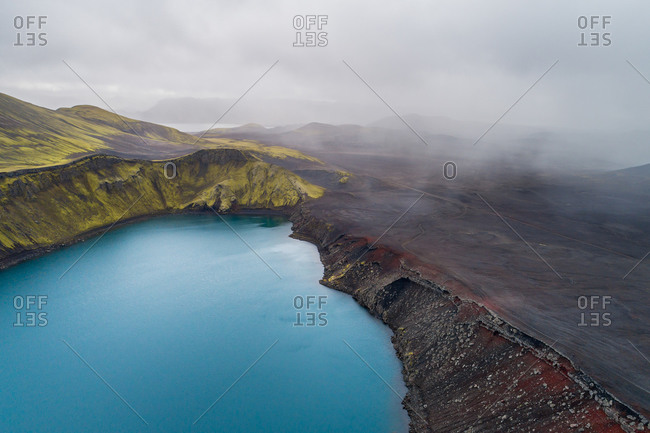 Aerial view of crater lake Blahylur, also known as Hnausapollur, with rainshowers, Fjallabak, highlands of Iceland