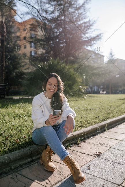 Brunette woman laughing as she checks her phone