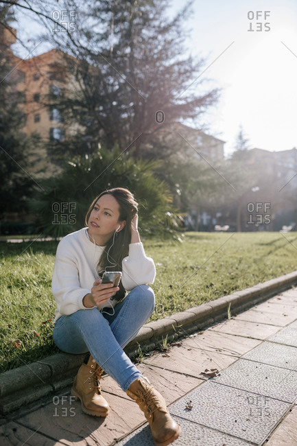 Caucasian woman taking a break and listening to music outside