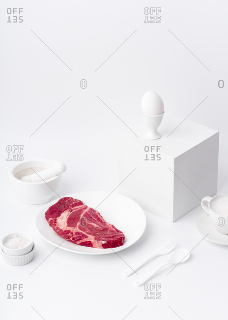Still life with white dishware and beef steak