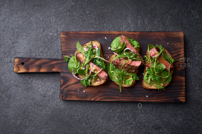 Top view shot of roast beef and arugula sandwiches on a dark background