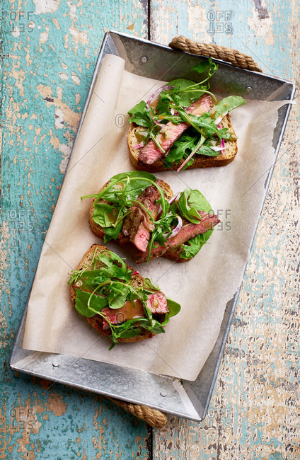 Top view shot of roast beef and arugula sandwiches on a rustic blue table