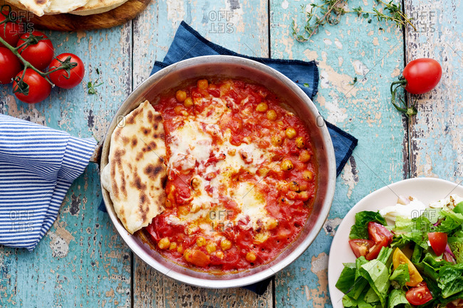 Baked chickpeas with tomato sauce and mozzarella served with salad and pita bread