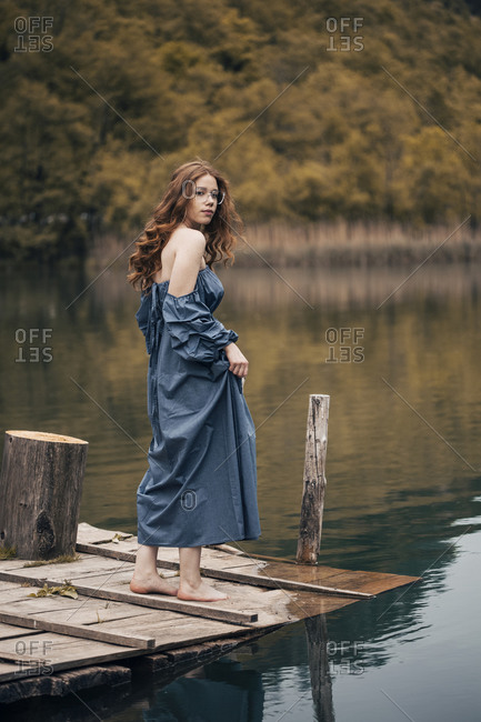 Ginger young woman standing on lake dock looking back
