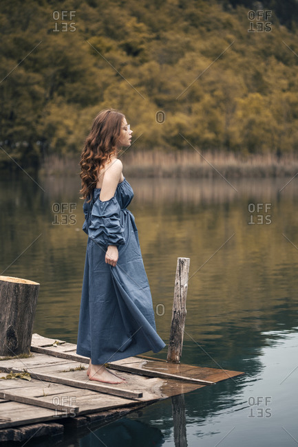 Ginger young woman posing on the lake dock in long blue dress