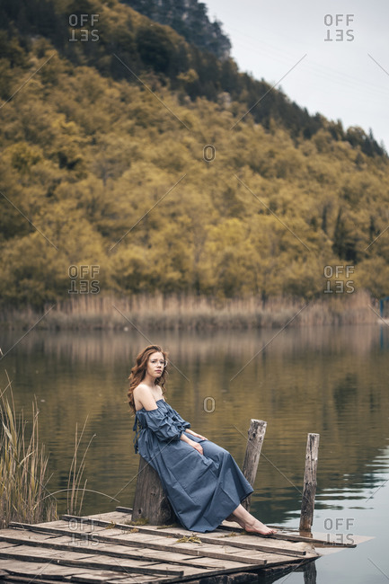 Young red haired woman posing on the lake dock in long blue dress