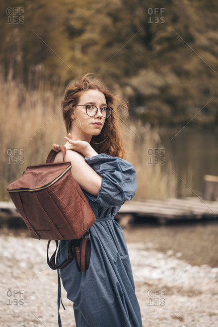 Ginger young woman posing on the lake with rucksack