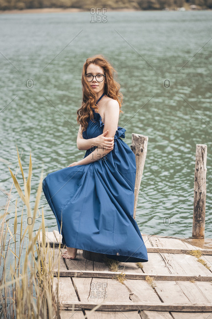 Young ginger woman posing on the lake dock in a long blue dress