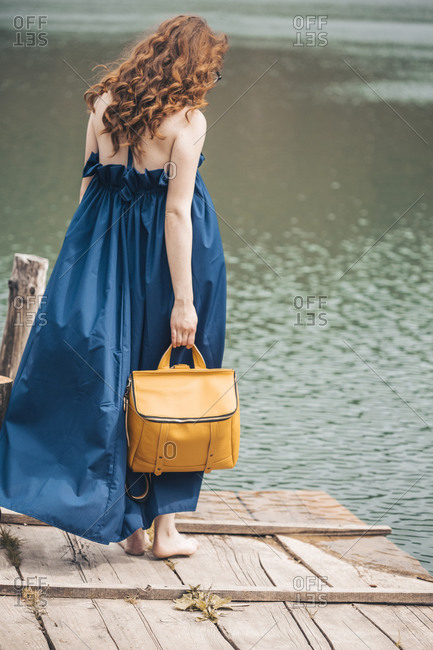 Ginger young woman on lake dock in long blue dress with a yellow rucksack
