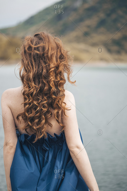 Back view of a ginger young woman overlooking the lake on a windy day