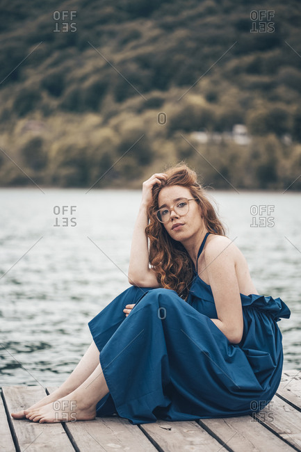 Ginger young woman sitting on the lake dock in blue long dress