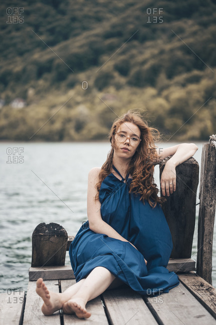 Redheaded young woman sitting on the lake dock in blue long dress